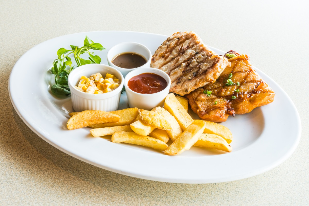 Pork chop and Chicken steak with french fries and sauce in white plate